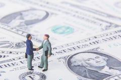 Transactie of overeenkomsten en succesconcept Twee miniatuurzakenlieden die handen schudden terwijl status op de Amerikaanse bede stock fotografie