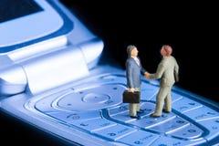 Transactie of overeenkomsten en succesconcept Twee miniatuurzakenlieden die handen schudden terwijl status op de sleutels van een stock afbeelding