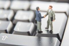 Transactie of overeenkomsten en succesconcept Twee miniatuurzakenlieden die handen schudden terwijl status op de sleutels van een royalty-vrije stock foto's