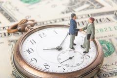 Transactie of overeenkomsten en succesconcept Twee miniatuurzakenlieden die handen schudden terwijl status op uitstekende oude kl stock foto
