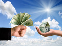 Transaction. Hand with a small house from banknotes Royalty Free Stock Photos