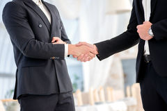 Transaction business. Two successful and confident businessman t. Alking in office shaking hands with each other Stock Photo