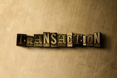 TRANSACTION - close-up of grungy vintage typeset word on metal backdrop Stock Photography