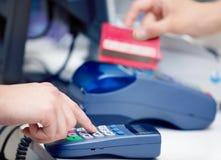 Transação do terminal da posição Mão que swiping um cartão de crédito Imagem de Stock