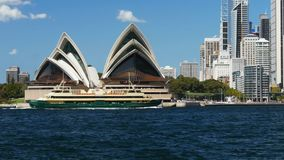 Transbordador de hombres que pasa delante del teatro de la ópera de Sydney metrajes