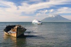 Transbordador de madera viejo delante de un volcán, Indonesia Fotos de archivo