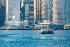 Transbordador de pasajero verde en el puerto de Victoria con el fondo del paisaje urbano contra salida del sol morining, servicio imagen de archivo