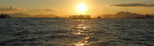 Transbordador a través del estrecho en la puesta del sol Imagenes de archivo