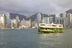 Transbordador y rascacielos en Hong Kong en la puesta del sol Fotos de archivo libres de regalías