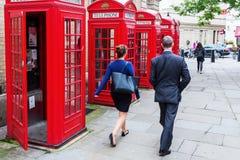 Transeúnte en el jardín de Covent, Londres, Reino Unido, en las cajas rojas tradicionales del teléfono Foto de archivo