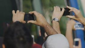 Transeuntes curiosos que filmam a celebridade perto do ônibus, desempenho de espera da música vídeos de arquivo