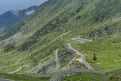 Transfagarasan - High altitude winding road in Carpathians mountains panorama with running cable car . Aerial view. Royalty Free Stock Photography