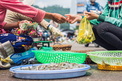 Transfer of goods and money in the Vietnamese market. Asian cuisine concept Stock Images
