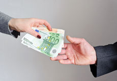 Transfer money from hand to hand. Female hand gives money, the man's hand takes them Stock Image