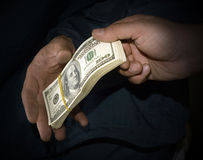 Transfer of money. From hands in hands in the dark tonality, symbolizing a bribe Stock Image