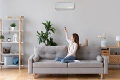 Transferencia de la mujer joven en el aire acondicionado que se sienta en el sofá imagen de archivo libre de regalías