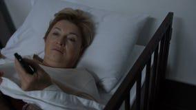 Transferencia femenina madura triste de la TV que miente en cama y que piensa en problemas de la vida almacen de metraje de vídeo
