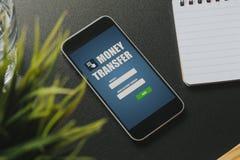Transferencia monetaria app en una pantalla del teléfono móvil sobre una tabla negra del negocio imágenes de archivo libres de regalías
