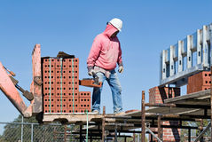 Transferring Brick. Construction worker transferring brick from fork lift to scaffolding Royalty Free Stock Image