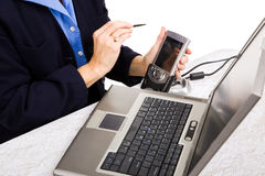 Transferring Business Data. Closeup of a businesswoman transferring data from her PDA to her laptop Stock Photography