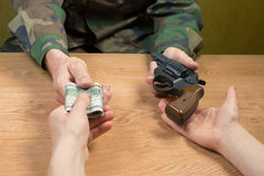 Transfers of money in exchange for a gun under certain conditions. Transfers of money in exchange for a gun under certain conditions, sitting at the table Royalty Free Stock Photography