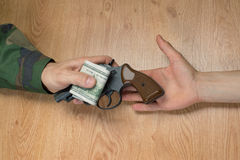 Transfers of money in exchange for a gun under certain conditions. Transfers of money in exchange for a gun under certain conditions, sitting at the table Stock Photo