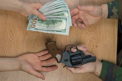 Transfers of money in exchange for a gun under certain conditions. Transfers of money in exchange for a gun under certain conditions, sitting at the table Stock Photography