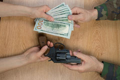 Transfers of money in exchange for a gun under certain conditions. Sitting at the table Stock Photos