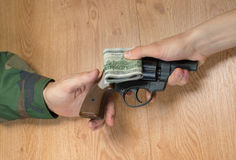 Transfers of money in exchange for a gun under certain conditions. Sitting at the table Stock Image