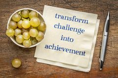 Transform challenge into achievement. Inspirational handwriting on a napkin stock image