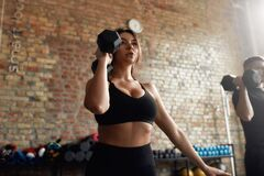 Free Transform. Young Focused Woman Exercising With Dumbbell While Having Workout At Industrial Gym. Group Training Concept Stock Image - 185542631