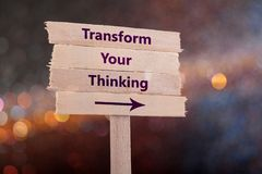 Transform your thinking. Wooden sign with boke background royalty free stock image