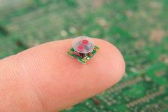 Transformador componente do RF da eletrônica pequena no dedo humano imagens de stock