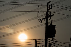 Transformador e linhas elétricas no polo bonde no por do sol Imagens de Stock
