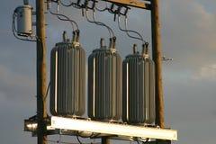 Transformadores de potência no por do sol Imagens de Stock