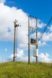Transformateur avec les poteaux de l'électricité dans le domaine Photo libre de droits