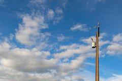 Transformateur sur un poteau de courant électrique (poteau de service) contre le bleu photographie stock