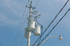 transformateurs électriques accrochant sur le poteau léger contre le ciel bleu-foncé Photo libre de droits