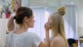transformation Im modischen Schönheitssalon bereitet ein Berufsmaskenbildner das Bild für eine attraktive Blondine vor stock footage