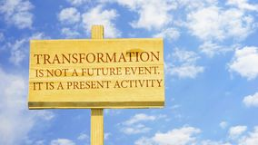 Transformation. Is not a future event, it is a present activity. Words on a wooden sign against time lapse clouds in the blue sky stock video footage
