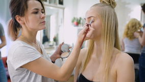 Transformation. In the trendy beauty salon, a professional makeup artist prepares the image for an attractive blonde. Client with a modern haircut stock video