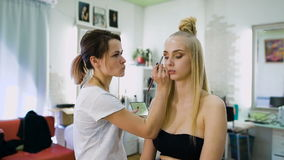 Transformation. In the trendy beauty salon, a professional makeup artist prepares the image for an attractive blonde. Client with a modern haircut stock footage