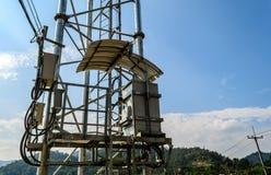 Transformator na Elektrycznych słupach z niebieskim niebem. Zdjęcie Royalty Free