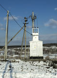 Transformatorowa podstaci podstacja energetyczna w zimie na tle wioska i niebieskie niebo Obraz Royalty Free