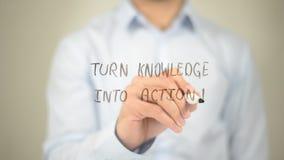 Transforme o conhecimento na ação, escrita do homem na tela transparente fotos de stock royalty free