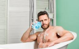 Transforme seu banheiro em pr?prios termas privados Macho com banho da tomada da esponja em casa Tomando o banho com Sul do sab?o fotos de stock royalty free
