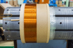 Transformer coil under production. Round enamelled wire being wound to form the transformer coil on the winding machine Stock Photo
