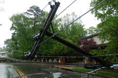 Transformer on a pole and a tree laying across power lines over a road after Hurricane moved across. Transformer on a electric poles and a tree laying across stock photography