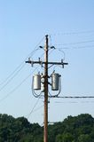 Transformers on a pole. Transformers for electricity mounted on a telephone pole in an industrial area, lines lead down to the buildings supplied by these Stock Images