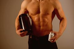Transforming body with diet. Anabolic hormone increases muscle strength. Strong man hold vitamin bottles. Man with six. Pack abs. Muscle growing with anabolic stock image